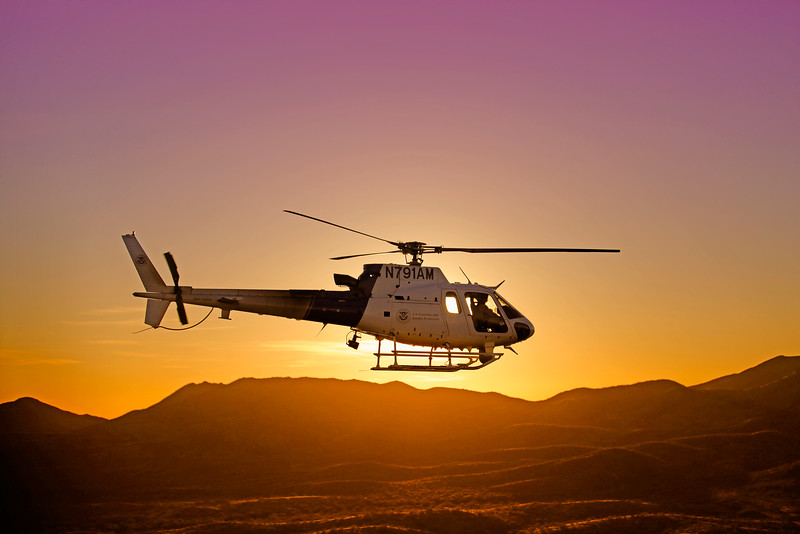An AS-350 Light Enforcement Helicopter (LEH) patrols the west desert of southern Arizona with the sunset over the Baboquivari Mountains and Tohono O'odham Indian Reservation.<br /> <br /> 9/29/2014<br /> Tucson Aviation Operations<br /> Airbus ASTAR AS-350 B3 2B1 791AM<br /> OMAHA 1AM<br /> FA1-15W Patrol<br /> By John E. Cottrell, AIA