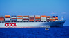 a container ship dwarfs a small fishing boat