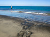 Footprints Leading to Ocean and Fly Fisherman