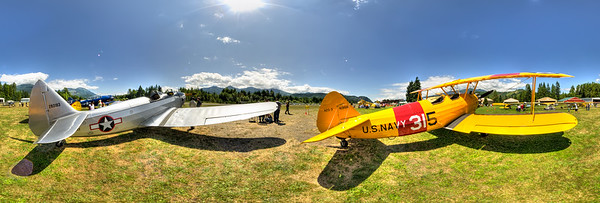North Cascades Vintage Fly-In, Stearman and Fairchild, Mears Field, Concrete, WA. Two vintage bi-planes, a Boeing-Stearman Model 75 Fairchild PT-19, sit together near the airstrip at Mears Field in Concrete, Washington at the annual North Cascades Vintage Fly-In. The Fairchild is part of the Skagit Aero Education Museum vintage aircraft collection, located at Mears Field.