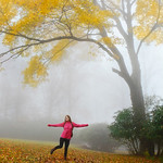 Girl enjoying beautiful autumn forest on foggy morning.