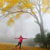 Girl enjoying beautiful autumn forest on foggy morning.