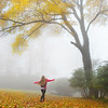 Girl enjoying day in foggy autumn forest.