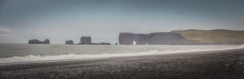 Dyrhólaey arch and lighthouse from black sand beach
