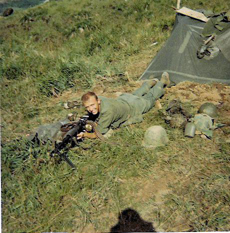 (TF4) Tommy Foley (WIA 8 Feb 68) in the boonies outside his poncho tent, prone with an M-60 machinegun