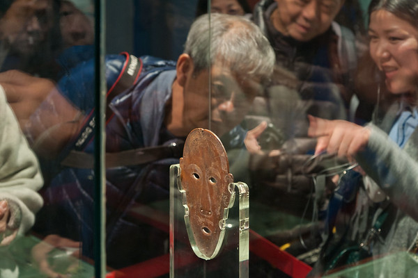 Jingzhou, Hubei Province.<br /> A docent at Jingzhou Museum points out the unique feature of this Warring States period jade burial mask: it is a carved and incised representation of a face on a single piece of jade. Typically facial features in ancient jade burial masks are faceted and composed of numerous jade pieces.