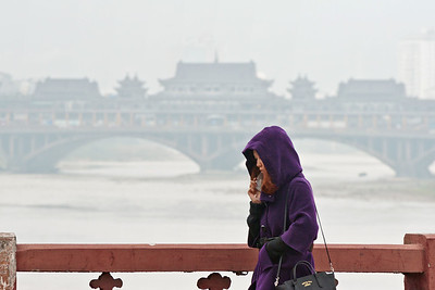 Ya'an, Sichuan Province.  A woman crosses over the Qingyi River, major tributary to the Lower Yangzi, on the Qiang River Bridge; downriver is the Yazhou Covered Bridge, a pedestrian mall with traditional Chinese architectural features surrounded by vehicular traffic, completed in 2005.