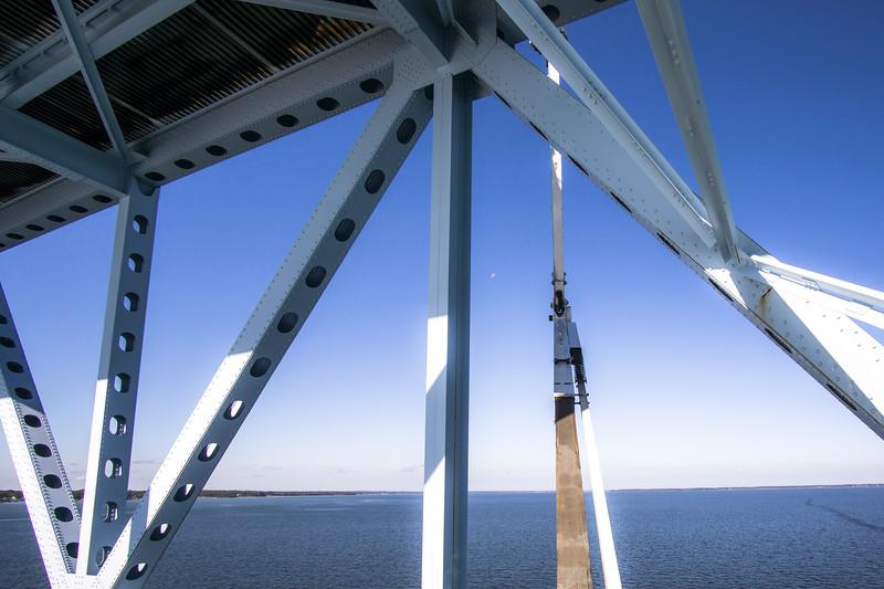 Moon overlooks at worker crews in the distance, through the steel, Robert O. Norris Bridge over the Rappahannock RIver in Virginia.