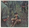 JF-82_A captured North Vietnamese Army (NVA) Prisoner Of War sits amid a circle of Company A grunts in the boonies