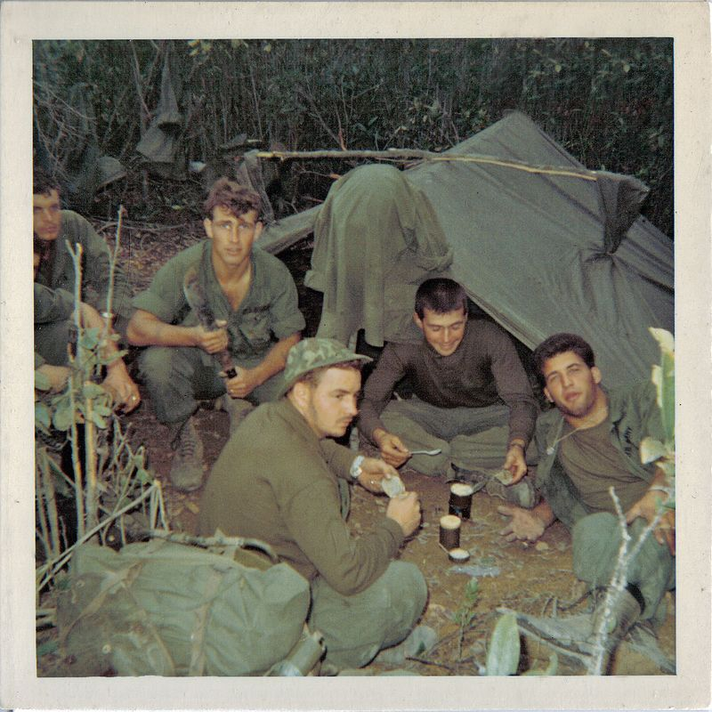 "JF-52_In the boonies, Bob Titus (CA), Victor ""Vic"" Girling (MN) with the machete, Joseph ""Pic"" Picarelli (NJ) in foreground in front of a poncho tent with C rations.  Captain Robert ""Bob"" Leinen, Sr. (MI) sitting crosslegged in front of the tent, and Angelo M. Galuppo (NJ) on his left. Pic was the CO's radio operator and was killed on 15 May 68. Vic spent 14 months in the field as the A Co Artillery Recon Sergeant. On 15 May 68, in a poorly conceived and fatal maneuver, Company A was directed to advance across a saddle between two hilltops on the Nui Hoac ridge south of LZ Center. The command group came under heavy fire, CPT Leinen jumped over a tree log to recover Picarelli.  Pic had gone over the log, got caught in an NVA crossfire, and was stuck in a exposed sitting position because his pack was hung on a tree stump.  Men were pulling on Pic, but he couldn't be freed until Leinen jumped over the log. Just as they got Pic over the log, Leinen, who was still on the exposed side of the log, got hit in both legs.  He was evacuated to Chu Lai, stabilized, and  sent to  Camp Zama, Japan.  He then went back to the states.  He couldn't walk for 6 months.  (Leinen and Pic also were wounded on 29 April, so each man got two Purple Hearts.)<br /> 	     George Meek, Arty FO For Co. A, says, ""I had never heard the story of how Capt. Leinen pulled Pic over the log.  It does not surprise me.  When I got to the scene, they were all lying down in the open and not moving.  After I put the artillery on the target we all moved out to get them to the MedEvac area.  Pic was still alive when we put him on his poncho.  I thought Capt. Leinen was dead, there was so much blood.  He did not seem to be responding at the time.  Anyway, Pic died before we got him to the helo pad.  Very sad, sad day. <br /> 	     ""I really respected CPT. Leinen and realized that he had some pretty big shoes to fill.  I can tell you that he made some great decisions that I think kept us out of harm's way more than once.  He was a great leader that day we took Hill 352.  <br /> 	     ""Another time I remember,"" said Meek, ""we were moving through some hills, very dense vegetation, and set up camp in the only reasonably defendable area.  Leinen made the gooks think that was where we would be.  At dusk he made us move up into a wooded area and sure enough  after it got dark the gooks hit where we had been.  <br /> 	     ""That was the night Pic stood out on the perimeter with the strobe light and kept our gunships from blowing us away.  It's where he earned his Silver Star.""  (Note the stick on the tent going from poncho hood to poncho hood--it kept rain from going down the hood and inside.)"