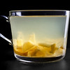 Glass cup of fresh lemon and ginger fruit tea isolated on black. Fruit pieces visible.