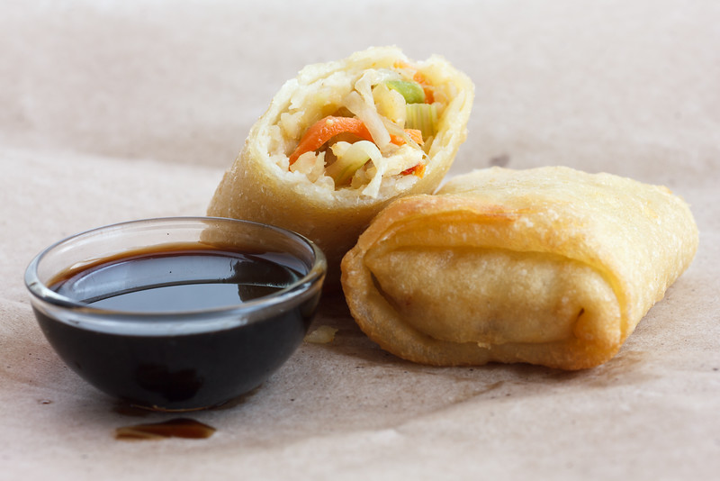 Single fried vegetable spring roll on wax paper with soya sauce.