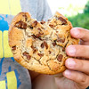 Child holding large homemade chocolate chip cookie.
