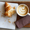 Half eaten croissant with cappuccino on wood tray from above.