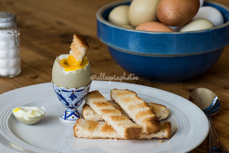 A soft boiled egg with strips of toast