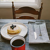 blueberry pancakes and coffee breakfast table.