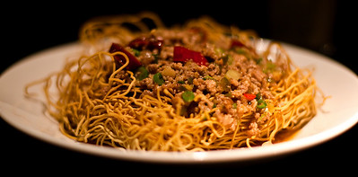 Stir fried spicy pork and fermented chilli with crispy fried noodles