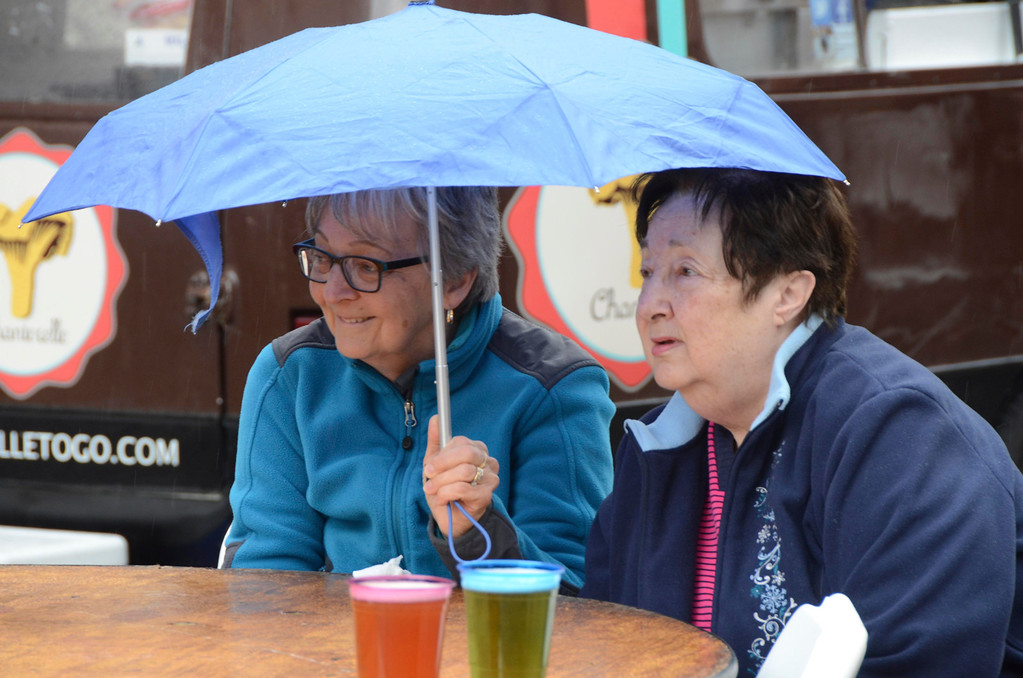 . From left, Marilyn Herrman and Rosemary Casey of Pittsfield share an umbrella during the food truck community event in Palace Park to benefit Moments House in Pittsfield on Sunday, May, 4, 2014. Gillian Jones / Berkshire Eagle Staff / photos.berkshireeagle.com