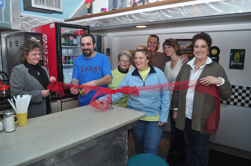 Co-owners of Izzy's Pizza and Deli in Adams, Richard Solomon and Ann Marie Belmonte, cut a grand opening ribbon with staff Thursday morning. (Jack Guerino/North Adams Transcript)