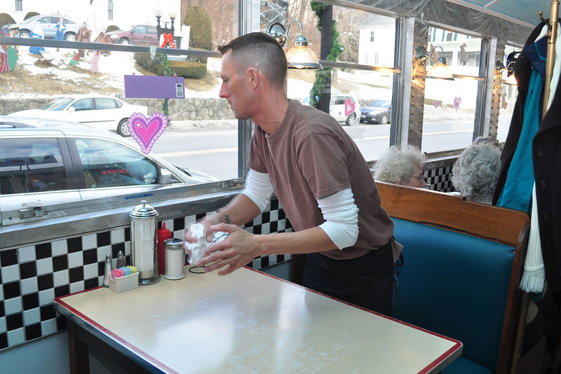 Aaron Volpi, from Adams, cleans up tables during the grand opening of Izzy's Pizza and Deli in Adams Thursday morning. (Jack Guerino/North Adams Transcript)