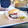 BEN GARVER — THE BERKSHIRE EAGLE<br /> A Box Burger is served hot off the grill to a customer at the Bistro box. The burger features tomato and bacon jam.