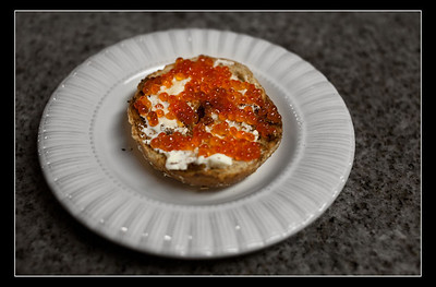 Cream cheese and red caviar served on a multi grain bagel.