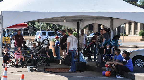 Tyler residents enjoy the shade of a tent while attending a community celebration marking the 70th Anniversary of The Village Bakery in Tyler.  The event included a children's Halloween costume contest, lunch and live music. (Jessica T. Payne/Tyler Morning Telegraph)