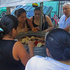 "These women pick through the fresh ""pan dulce"" offered up by the vendor in the square."