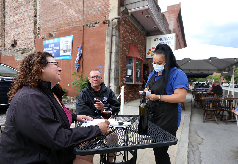 Athenian Corner restaurant is open for outdoor dining as part of phase 2 of reopening the economy during the COVID-19 pandemic. Server Leyla Apache of Lowell takes the order of Celeste and husband Bob Dunn of Chelmsford. (SUN/Julia Malakie)
