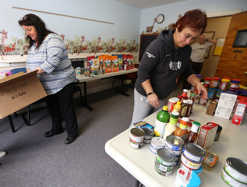 Diana Sounders, left, and Taryn Gillis, both of Billerica, pick out items for customers at the Emergency Food Pantry at First Congregational Church in Billerica. The next regular Billerica Food Pantry is not until March 30, and the Marshall Middle School food pantry that was scheduled for this past Thursday was cancelled as Billerica schools were closing on Friday. (SUN/Julia Malakie)