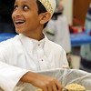 Volunteers package meals of rice, pinto beans, soy, dried vegetables, seasoning and vitamins, organized by The Outreach Program, at Anjuman-e-Ezzi in Billerica. Aamir Dohadwala, 12, of Reading, one of the organizers, scoops rice. (SUN/Julia Malakie)