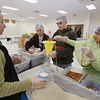 Volunteers package meals of rice, pinto beans, soy, dried vegetables, seasoning and vitamins, organized by The Outreach Program, at Anjuman-e-Ezzi in Billerica. From left, Karen Frost, her daughter Avery Frost, 12, son Logan Frost, 14, of Billerica, and Munira Dhilla of Acton, measure portions. (SUN/Julia Malakie)