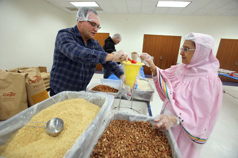 Volunteers package meals of rice, pinto beans, soy, dried vegetables, seasoning and vitamins, organized by The Outreach Program, at Anjuman-e-Ezzi in Billerica. Billerica police chief Dan Rosa and Rubab Dahod of North Andover measure ingredients. (SUN/Julia Malakie)