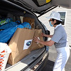 CMAA hosts event with the Buddhist Tzu Chi Foundation to distribute bags of food to 300 families. Evelyn Baratham of Lowell, who is with Tzu Chi, puts bags in a car. (SUN/Julia Malakie)
