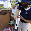 CMAA hosts event with the Buddhist Tzu Chi Foundation to distribute bags of food to 300 families. Vickie Chang of Cambridge shows what's in each bag, including rice that's already cooked and can be ready to eat just by adding water, if there's no power to boil water. (SUN/Julia Malakie)