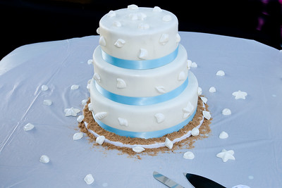 """3 Layer white pearl fondant cake with strawberry filling. White chocolate sea shells, and star fish adorn this cake. Brown sugar """"sand"""" complete this beach theme elegant cake."""