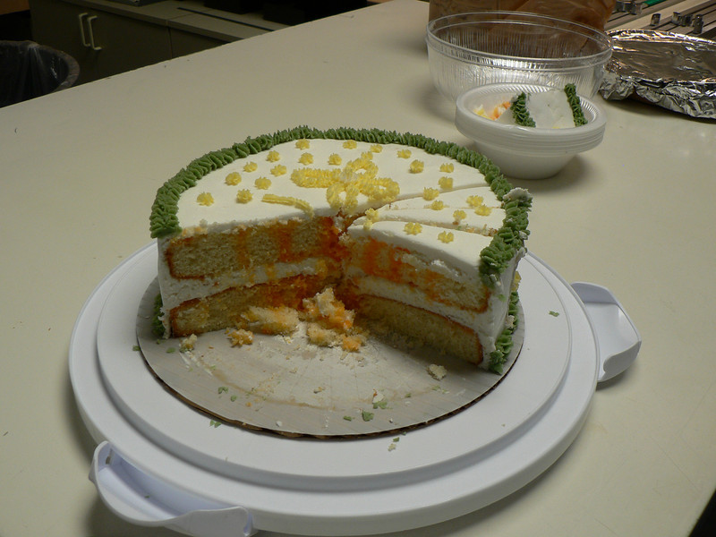 Orange Blossom Cake.  This one was created of May 13 and 14.  It is a vanilla cake infused with orange jello mix.  I created a vanilla cake according to package directions (2- 9in rounds).  While the cakes were cooling I created a orange mixture by mixing a package of orange jello with one cup of hot water.  After the cakes had cooled, I poked holes in the top of the cakes and spooned the orange mixture over the top of them.  I stored the cakes in the refrigerator over night.  The next day, I went over to Cathy and Robert's house.  Cathy showed me how to make buttercream frosting.  I flavored the frosting with orange extract.