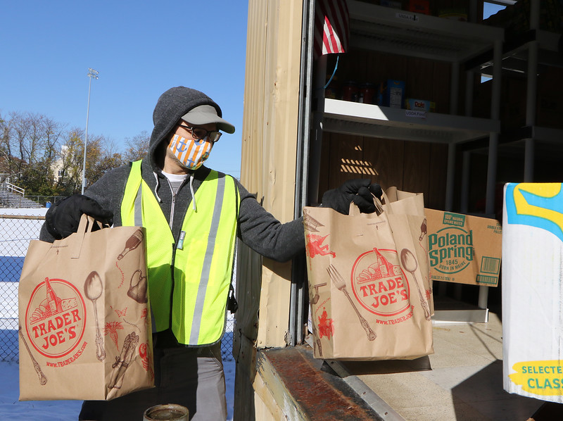 Drop-off at Chelmsford Food Pantry for food drive sponsored by State Rep. Tom Golden.  Volunteer Craig Bonaceto of Chelmsford moves donated bags of food.  (SUN/Julia Malakie)
