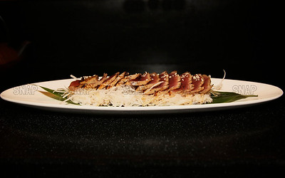 Soy Marinated Tuna: Yellowfin Tuna, Sushi Rice, Onions finely cut, sesame seeds, on a bamboo leaf.
