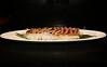 Soy Marinated Tuna: Yellowfin Tuna, Sushi Rice, Onions finely cut, sesame seeds, on a bamboo leaf.