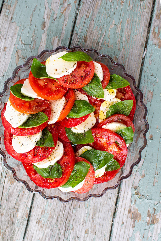 Tomato, mozzarella, and basil leaves layered in a tart dish.