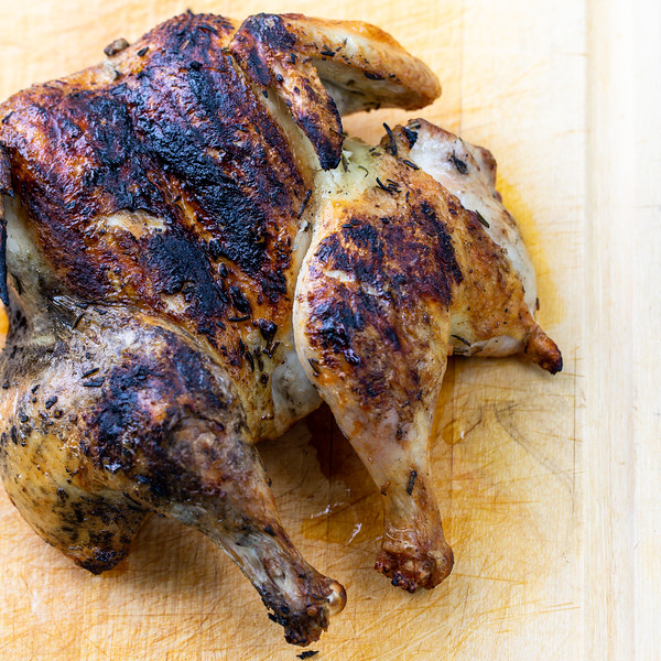 Grilled spatchcocked chicken on a wooden cutting board.