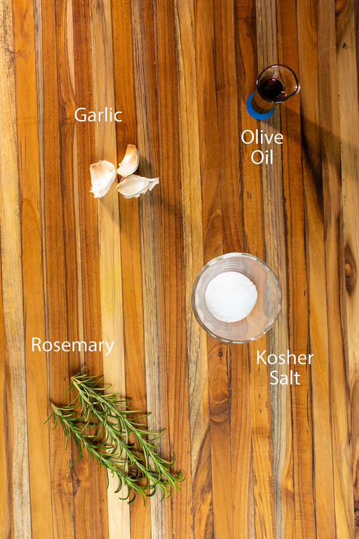 Garlic, olive oil, kosher salt and rosemary on a wood cutting board.