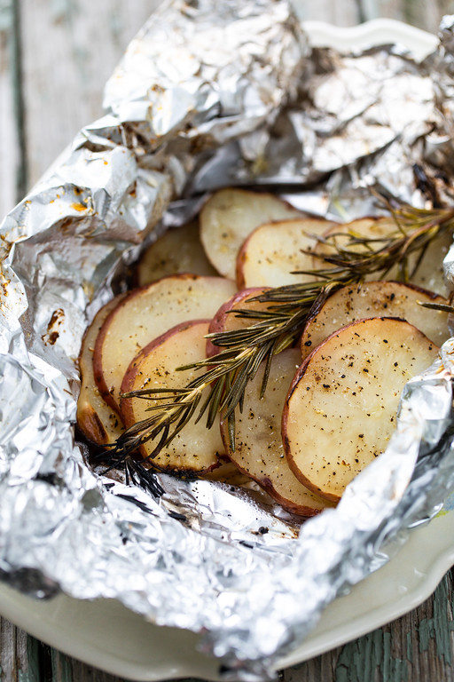 Sliced potatoes topped with a sprig of rosemary in a an open foil packet.
