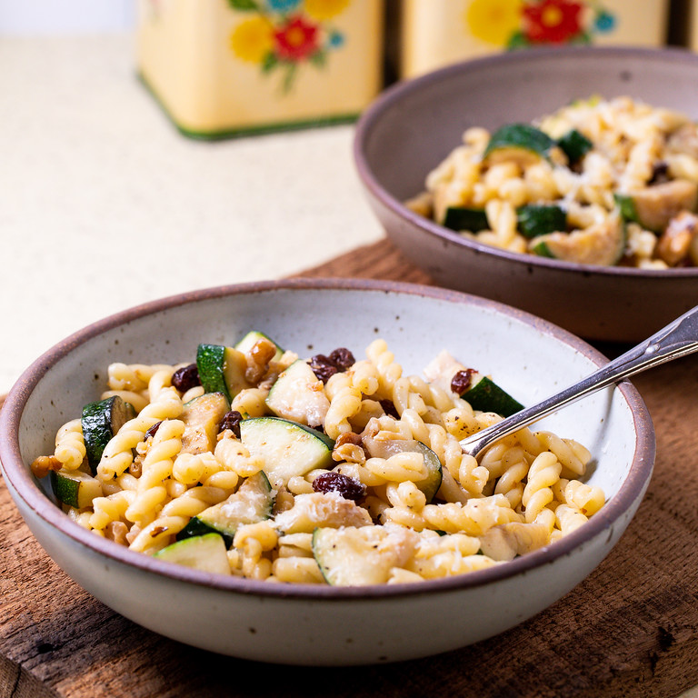 Bowl of pasta with zucchini, raisins and walnuts.