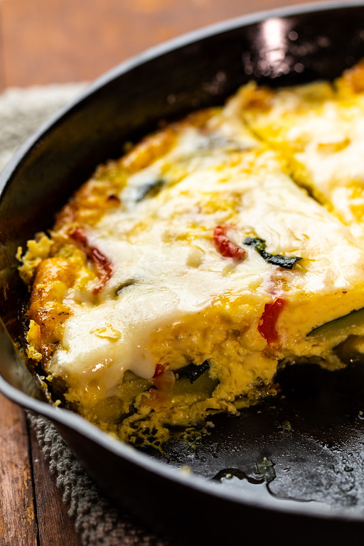 Close up the cut frittata with melted cheese.