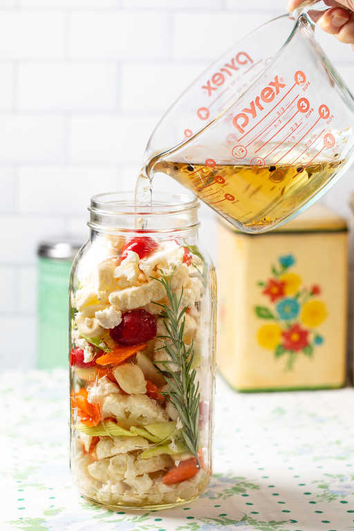 Brine solution being poured over large jar of chopped vegetables.