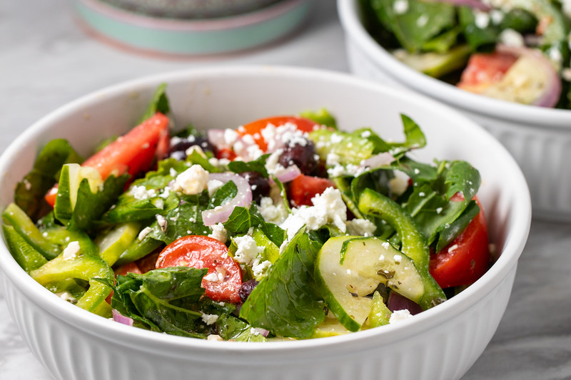 Close up of Greek salad in a white bowl.
