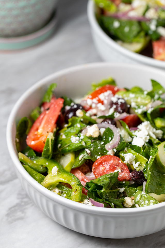 Greek salad with lettuce in a white bowl.