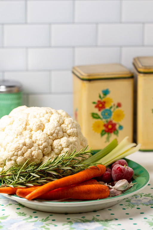 Plate with cauliflower, rosemary, carrots, celery, peppers, and garlic.